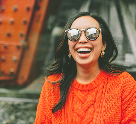 Young woman wearing sunglasses and an orange sweater