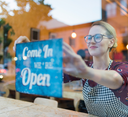 "Young woman in an apron holding up a ""come in, we're open"" sign in a window"