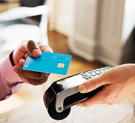 A hand holding a credit card up to a card reader