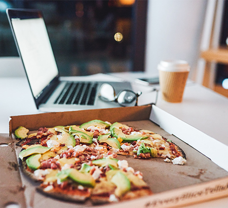 Bacon avocado pizza in a pizza box, next to a laptop, glasses, and coffee cup