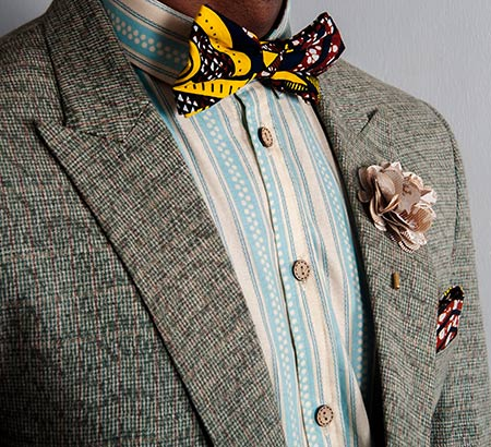 Torso of a dad wearing a hip, colorful blazer, bowtie, button-up shirt, and boutonniere.