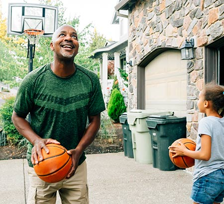 Father and daughter playing basketball in the driveway