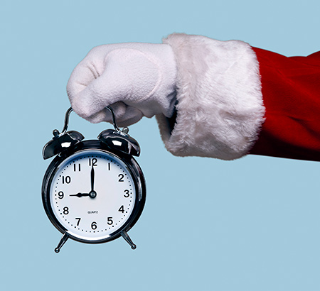 Santa's hand holding a silver alarm clock
