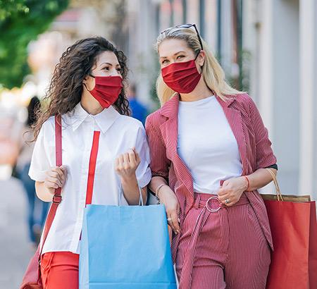 Two young women wearing masks walking down the street carrying shopping bags