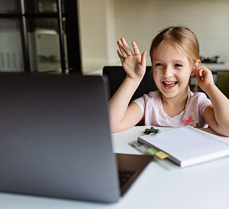 Little girl waving at her computer