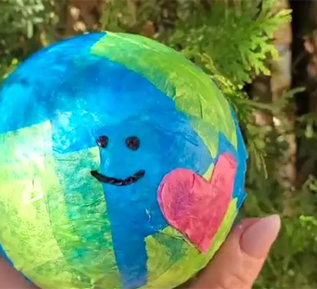 A hand holding the Earth Month Globe craft