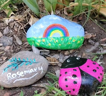 Three completed painted rocks crafts displayed in a garden: One painted with a rainbow, one with the word Rosemary and a rosemary sprig, and a pink ladybug
