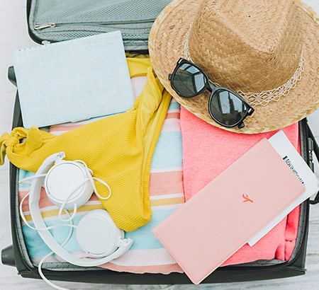 A suitcase packed with women's pastel clothes, headphones, sunglasses, straw hat, notebook, and airplane tickets