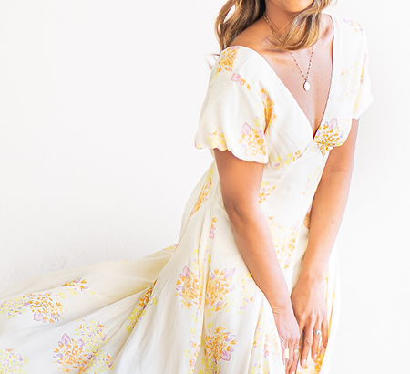 Woman wearing a long, flowy dress with a floral pattern