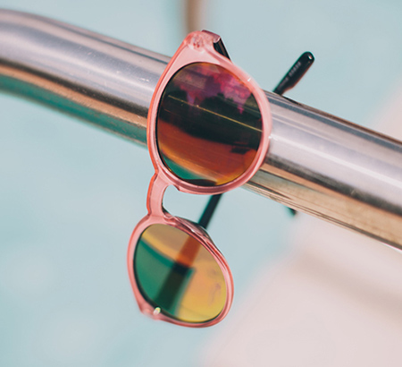 A pair of pink-framed sunglasses on a metal bar