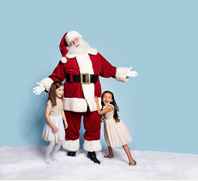 santa smiling with two young girls in white dresses on snow