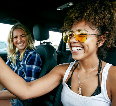 Two smiling women driving