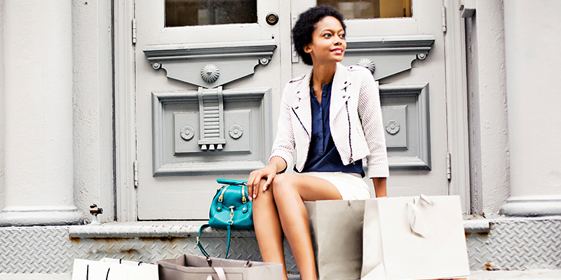Stylish woman sitting on a stoop surrounded by shopping bags