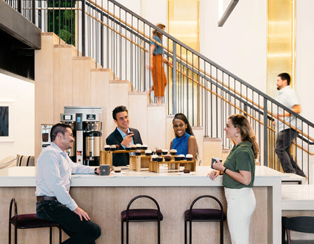 staff sitting at a coffee bar with cupcakes