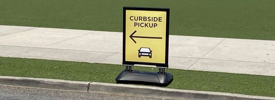 "Sign that reads ""Curbside Pickup"" with an arrow pointing to the left and a car illustration"