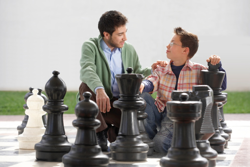 A man and child playing with large chess pieces