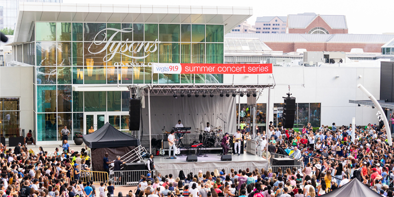 The Plaza entrance with a crowd gathered around a stage and live music performance.