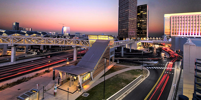 The Tysons Corner Metro stop entrance located adjacent to Tysons Corner Center at night with traffic driving by.