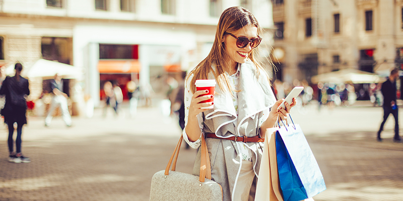 Woman texting, holding coffee and shopping bags