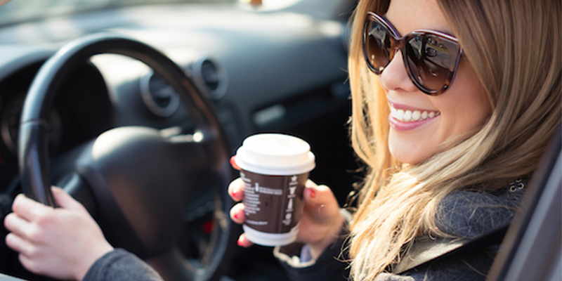 woman in a car drinking coffee