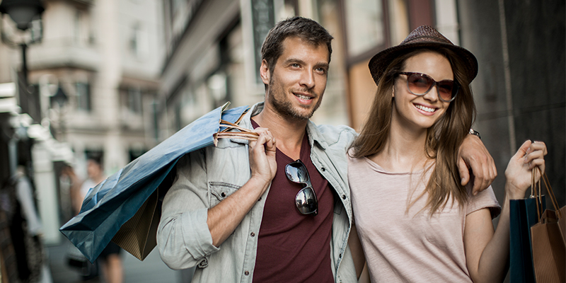 Man and woman smiling, holding shopping bags