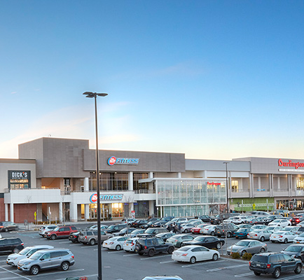 View of the exterior of Green Acres Commons, with Dick's Sporting Goods, 24 Hour Fitness, and Burlington