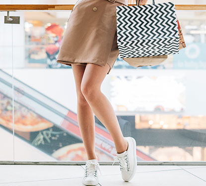 Legs of a woman carrying shopping bags and wearing white sneakers and a tan trench coat.