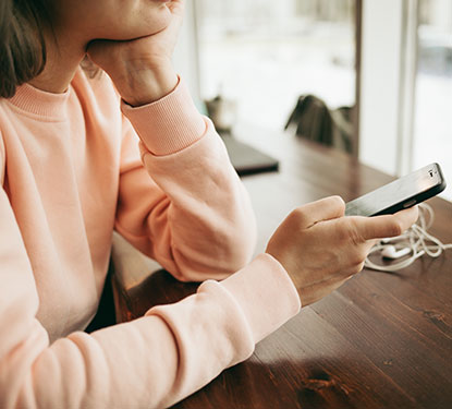 Woman wearing a light pink sweatshirt at a coffee bar looking at her phone