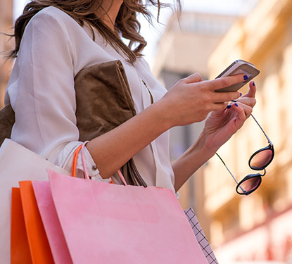 Woman texting on a phone carrying shopping bags and sunglasses