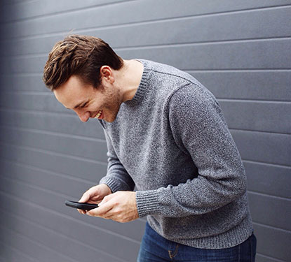 Smiling man in a gray sweater looking at his phone