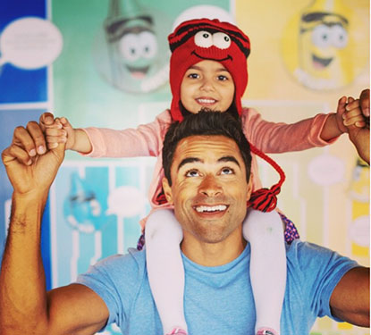 Little girl with a red crayon knit hat sitting on dad's shoulders in front of a Crayola Crayons background