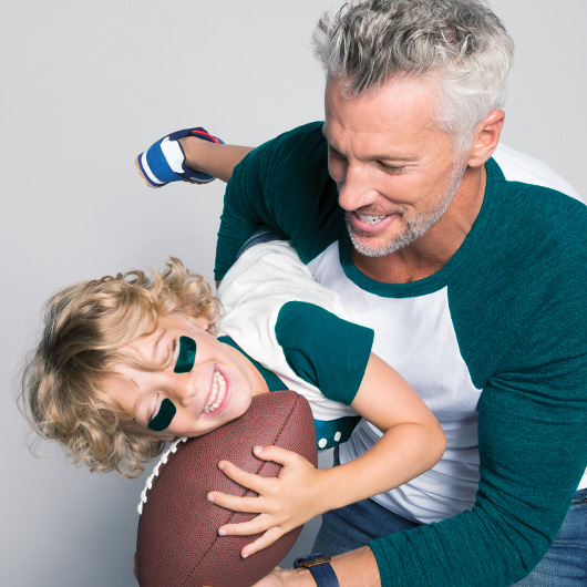 Man holding a small girl and boy in his arms