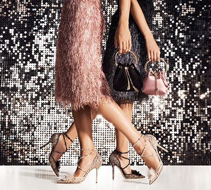Two models in Jimmy Choo shoes carrying purses