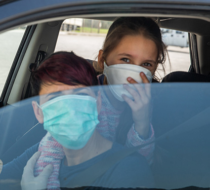 Two teens in a car wearing masks awaiting a COVID test