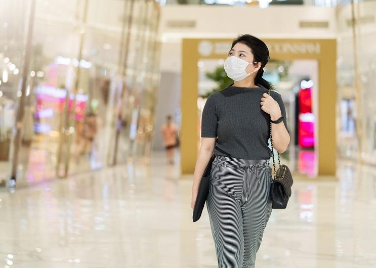 lady walking through mall, wearing a mask
