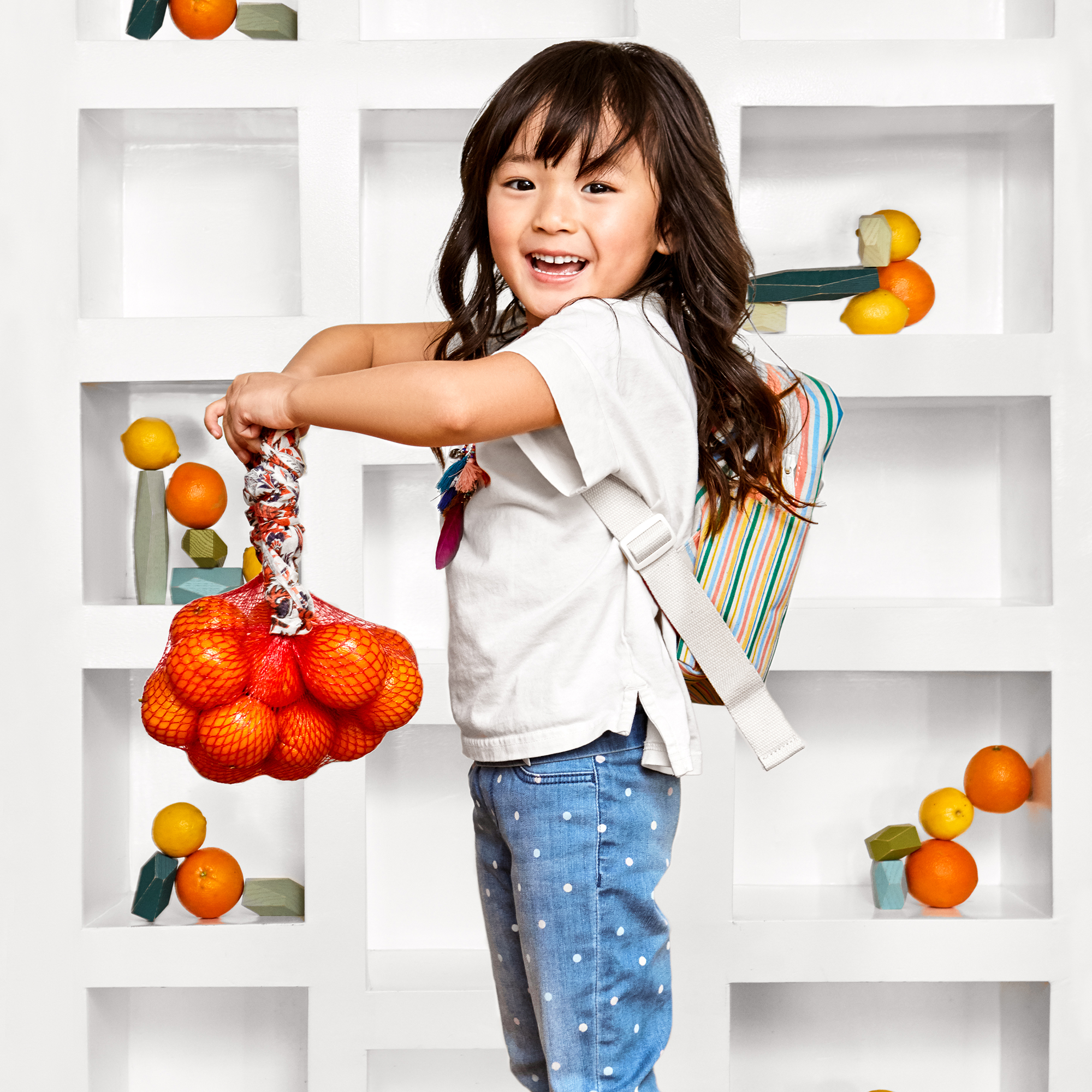 girl holding a bag of oranges