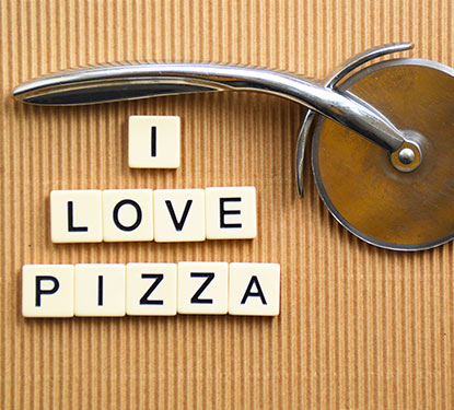 """Scrabble letters spelling out """"I Love Pizza"""" with a pizza cutter"""