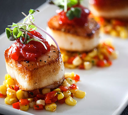 Seared scallops served with assorted vegetables