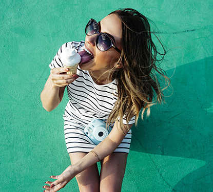 Woman eating an ice cream cone in front of a teal wall