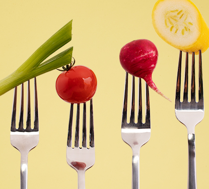 Four forks pointing upwards with a vegetable on each one