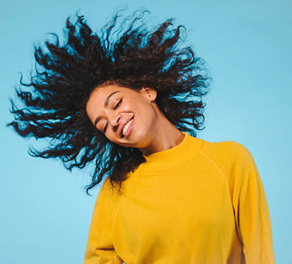 Smiling woman in a yellow sweater tossing her hair