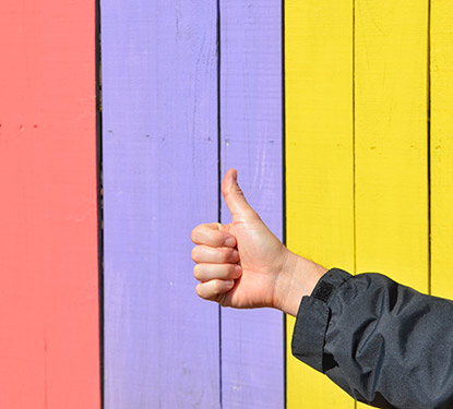 Hand giving a thumbs up in front of a multicolored fence