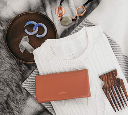 Flat-lay of sweater, earrings, comb, clutch, and crystals