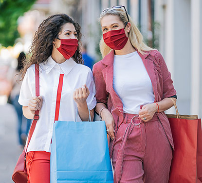 Two women carrying shopping bags while wearing masks