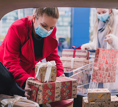 Woman in mask putting gifts into car