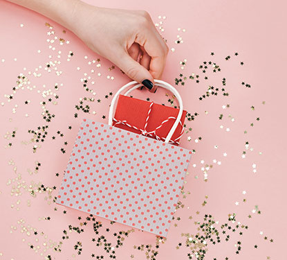 Tiny pink polka dot shopping bag with gold star confetti against a pink background