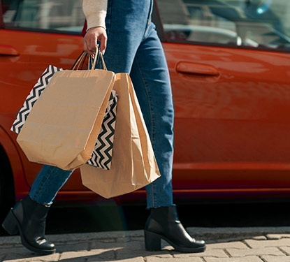 A woman wearing jeans and black boots carrying shopping bags to her car
