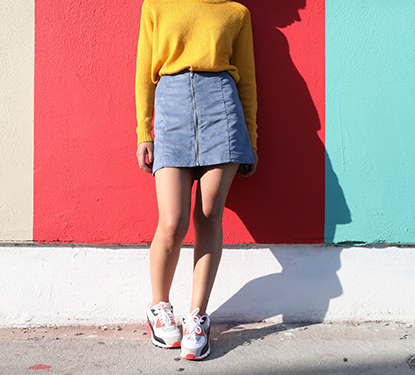 woman wearing a skirt and sneakers in front of a brightly colored, striped wall
