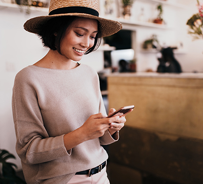 Woman wearing a straw hat texting