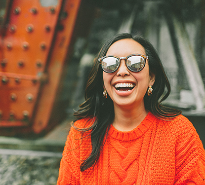 Laughing woman wearing sunglasses and an orange sweater